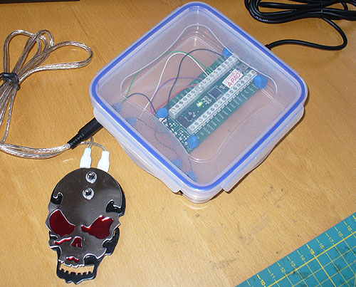 Image of a DIY Assistive Technology Lunch Box Interface, pictured with a DIY skull pedal.