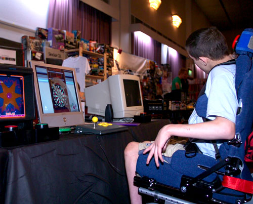 Accessible Gaming Museum. Chris Myers playing one-switch accessible Shenmue Darts at a gaming convention.